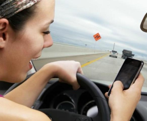 young woman driving on highway while reading / writing text on smart phone.