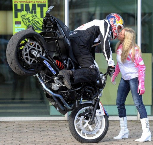 epa02552212 Motorcycle stunt champion Chris Pfeffier (L)and model Mai-Lin perform a 'Stoppie-Kiss' trick at the Hamburg Motorcycle Days trade show in Hamburg, Germany, 27 January 2011. The 17th Hamburg Motorcycle Days takes place from 28 to 30 January 2011 with many exhibitions and shows.  EPA/MAURIZIOGAMBARINI
